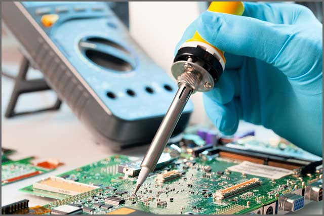 An image of a person soldering a PCB