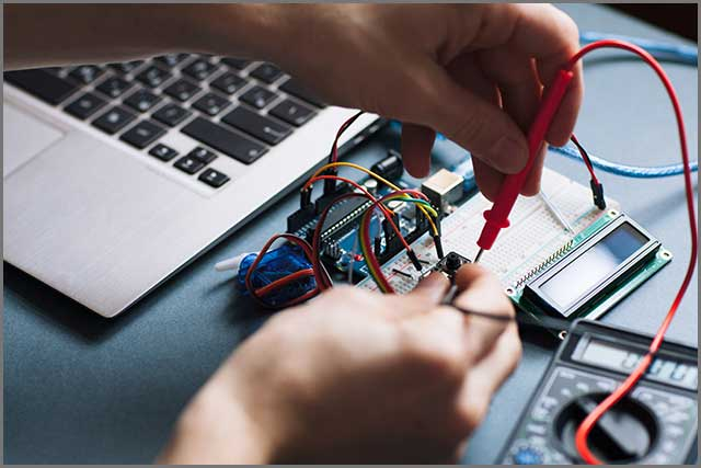 An image of a person closely examining a PCB