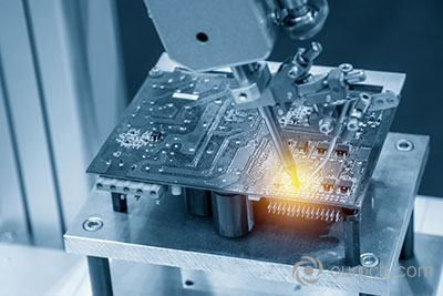 The welding robot solders the circuit board in a light blue scene with lighting effects