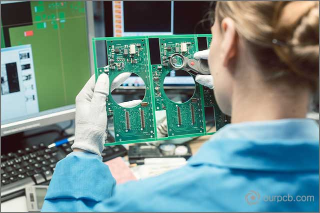 A technician in a prototype PCB supplier's workshop inspecting quality standards