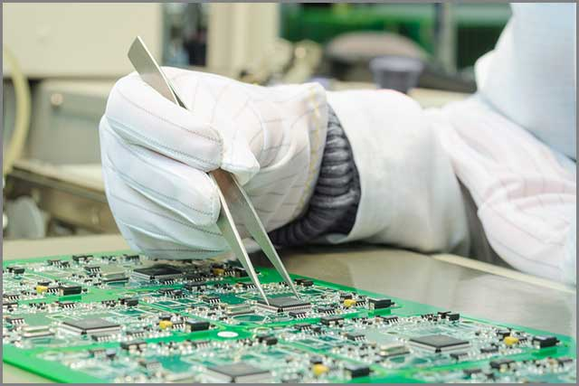 Circuit board maker carrying out quality control procedure on a PCB