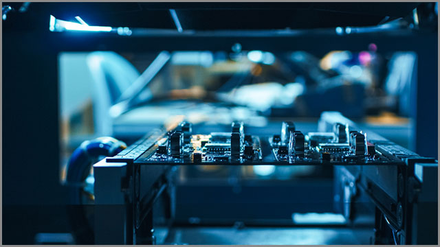 After assembly, automated robotic equipment is using light and laser technology to test electronic printed circuit boards